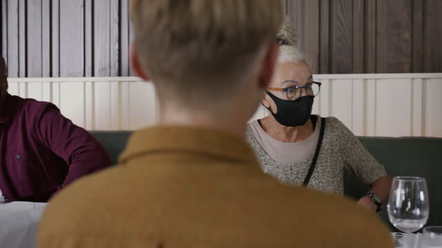 senior woman arriving at restaurant and removing face mask - infectious disease stock videos & royalty-free footage