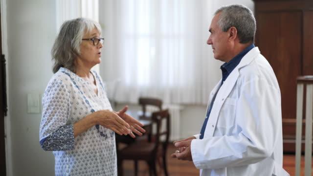 seniorin bittet ihren arzt im pflegeheim um rat - hausbesuch stock-videos und b-roll-filmmaterial