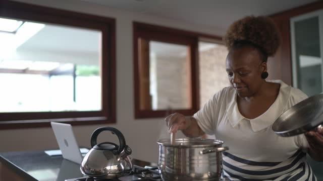 vídeos de stock, filmes e b-roll de idosa em casa cozinhando - afro