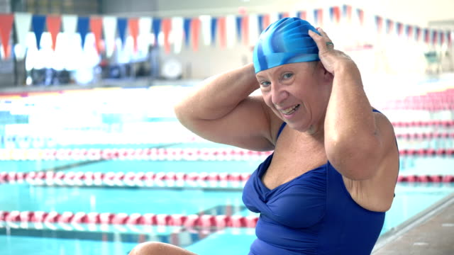 senior woman at indoor swimming pool on deck - swimming cap stock videos & royalty-free footage