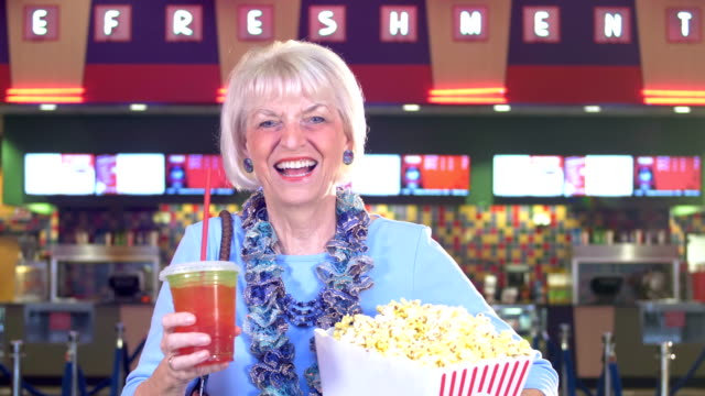 senior woman at movie theater concession stand - lobby stock videos & royalty-free footage