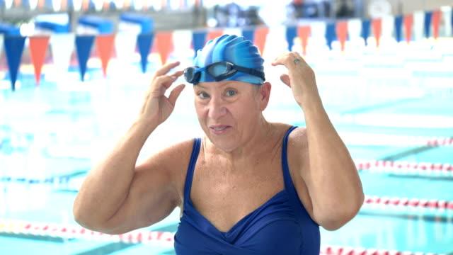 senior woman at swimming pool preparing to swim laps - swimming cap stock videos & royalty-free footage