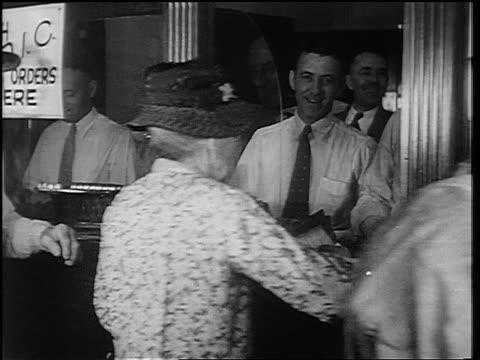 b/w 1934 rear view senior woman at teller window in fon du lac bank / east peoria, il / newsreel - cashier stock videos & royalty-free footage