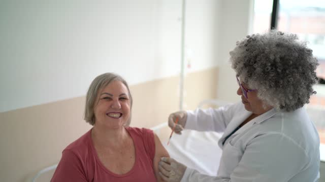 vídeos y material grabado en eventos de stock de mujer de la tercera edad vacunada - epidemiología