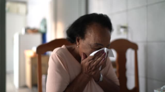 vídeos de stock e filmes b-roll de senior woman blowing her nose at home - brazilian ethnicity
