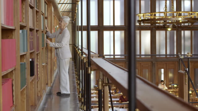 DS Senior woman browsing books on library balcony