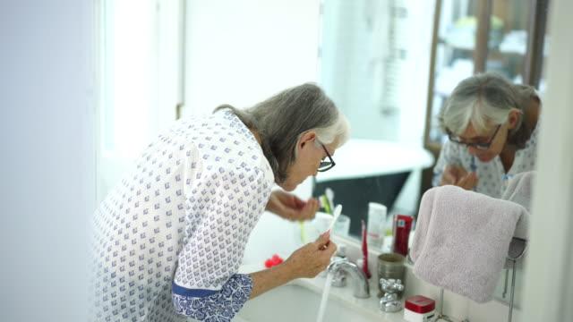 senior woman brushing her teeth in bathroom - routine stock videos & royalty-free footage