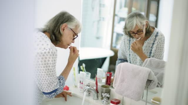 senior woman brushing her teeth in bathroom - brushing stock videos & royalty-free footage