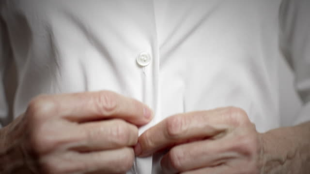 cu senior woman buttoning white shirt / new york city, new york, usa - oberhemd stock-videos und b-roll-filmmaterial