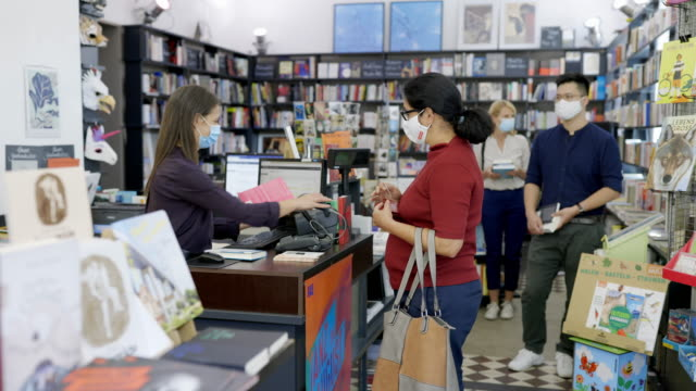 senior woman buying books at bookstore during pandemic - arts culture and entertainment stock videos & royalty-free footage