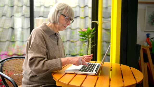 vídeos de stock e filmes b-roll de senior woman buying from internet - usar computador