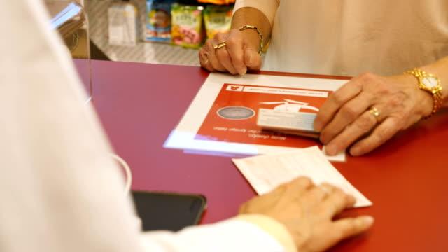 年配の女性が店で薬局から薬を購入 - 女性患者点の映像素材/bロール