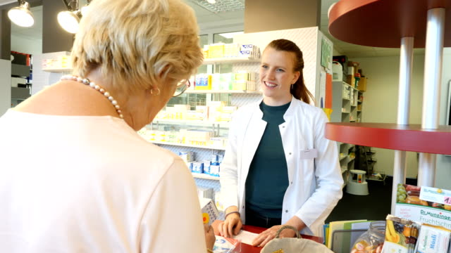 senior woman buying medicine from pharmacist - magazine stock videos & royalty-free footage