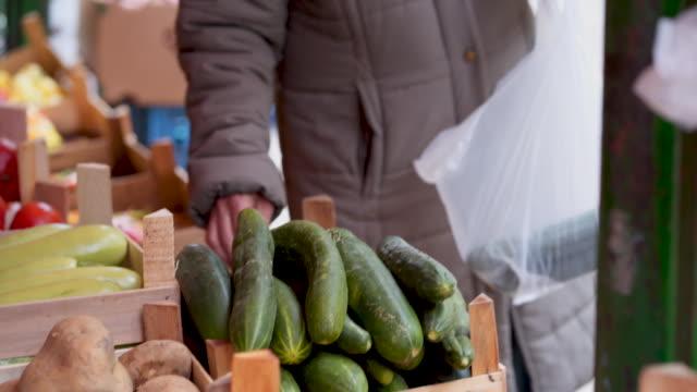 senior woman buying vegetables on marketplace - mercato di prodotti agricoli video stock e b–roll