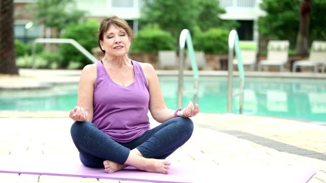 vídeos de stock, filmes e b-roll de mulher sênior piscina praticando ioga - exercício respiratório