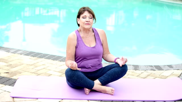 senior woman by pool practicing yoga - 60 69 years stock videos & royalty-free footage