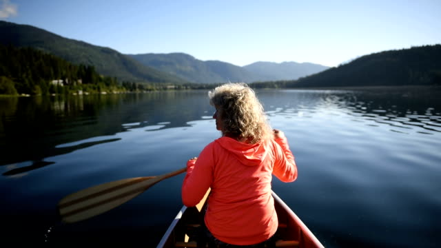 senior woman canoeing on a pristine lake - gray hair stock videos and b-roll footage