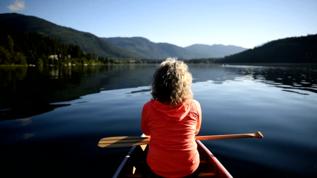 senior woman canoeing on a pristine lake - pagaiare video stock e b–roll