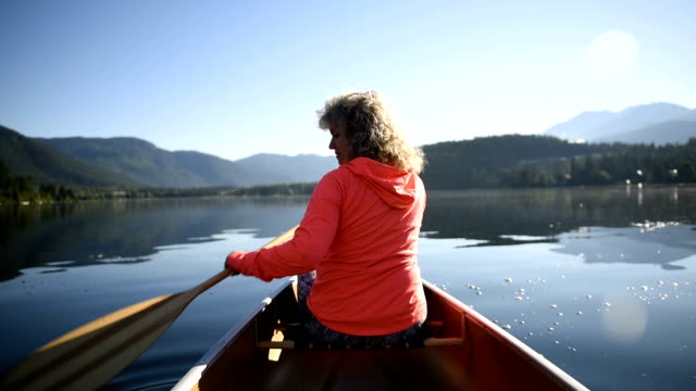 senior woman canoeing on a pristine lake - canoeing stock videos and b-roll footage