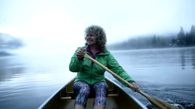 senior woman canoeing on a pristine lake - grey jacket stock videos and b-roll footage