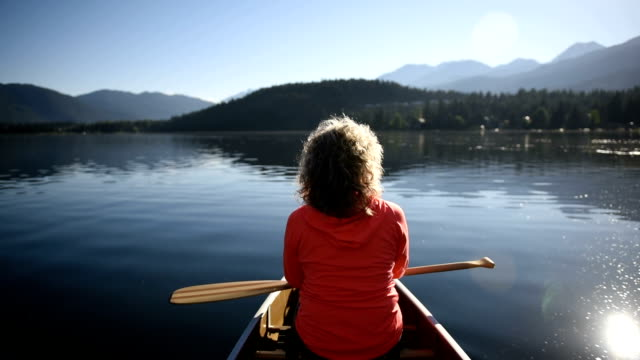 Senior Woman canoeing on a pristine lake