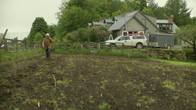 ws pan senior woman carrying hoe over shoulder and walking in empty garden patch / stowe, vermont, usa  - garden hoe stock videos & royalty-free footage