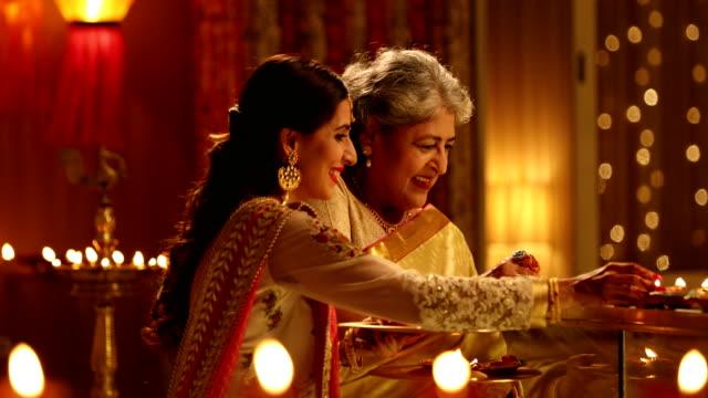 senior woman celebrating diwali festival with her daughter, delhi, india - 盆点の映像素材/bロール
