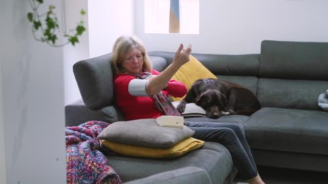 senior woman checking blood pressure on sofa - blood pressure gauge stock videos & royalty-free footage