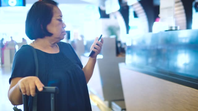 senior woman checking her flight on smart phone at airport - id card stock videos and b-roll footage