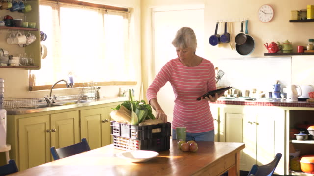 senior woman checking her fresh vegetable delivery - unpacking stock videos & royalty-free footage