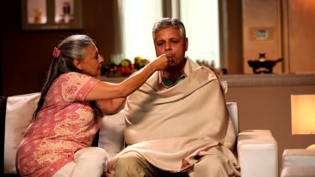 vídeos de stock e filmes b-roll de senior woman checking her husband temperature, delhi, india - cold temperature