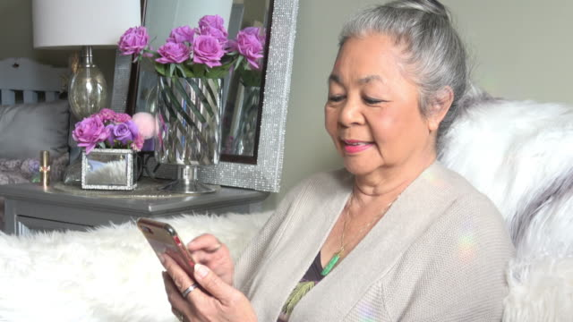 senior woman checking her smart phone - pacific islander stock videos & royalty-free footage