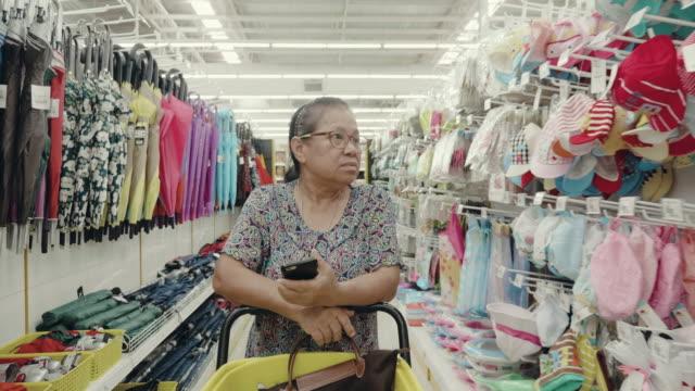 Senior Kvinna kontrollera inköpslista i snabbköpet.