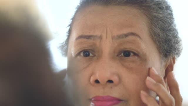vidéos et rushes de femme senior vérification peau miroir - miroir ancien
