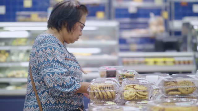 senior woman choosing bakery products on the shelves in the store - bakery stock videos and b-roll footage