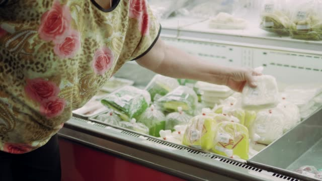 senior woman choosing vegetable at the grocery store. - frozen video stock e b–roll