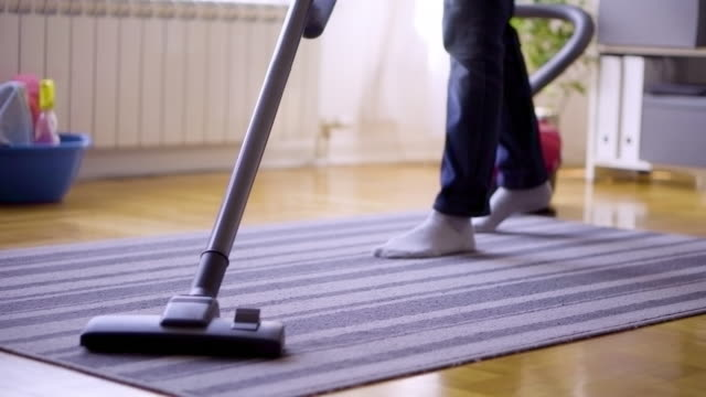 senior woman cleaning carpet with a vacuum cleaner at home - vacuum cleaner stock videos & royalty-free footage