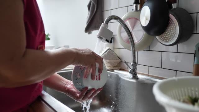 vídeos de stock e filmes b-roll de senior woman cleaning dishes with sponge at home. - lavar louça