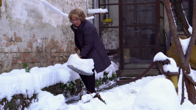 senior woman cleaning snow in her back yard - spade stock videos & royalty-free footage