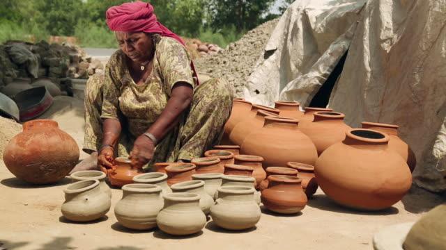 Senior woman colouring earthen pot, Haryana, India