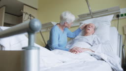 Senior woman comforting restless husband in hospital bed
