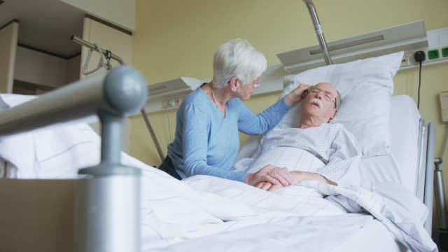 vídeos de stock e filmes b-roll de senior woman comforting restless husband in hospital bed - morte