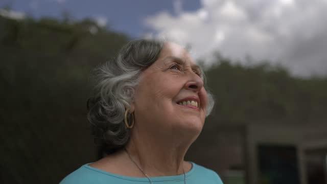 vídeos y material grabado en eventos de stock de mujer mayor contemplando en casa - mirar por la ventana