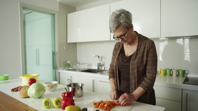 senior woman cooking a healthy meal - happy meal stock videos and b-roll footage
