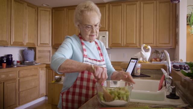 senior woman cooking at home - 年配の女性点の映像素材/bロール
