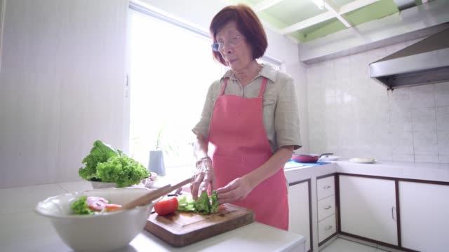 台所で健康的な食べ物を調理する先輩女性 - 台所点の映像素材/bロール