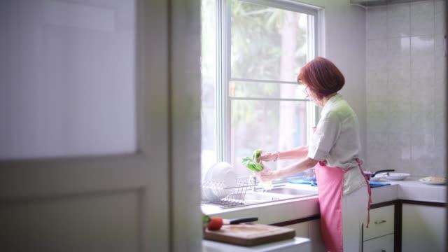 台所で健康的な食べ物を調理する先輩女性 - 年配の女性点の映像素材/bロール