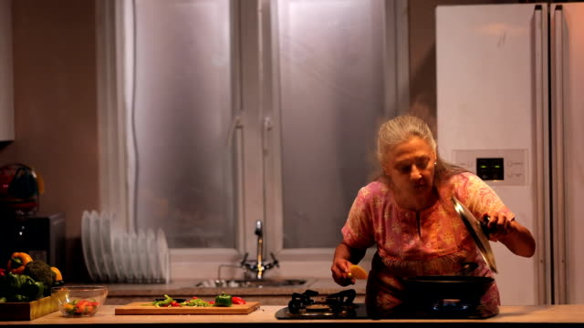 vídeos de stock e filmes b-roll de senior woman cooking in kitchen, delhi, india - fazer um favor