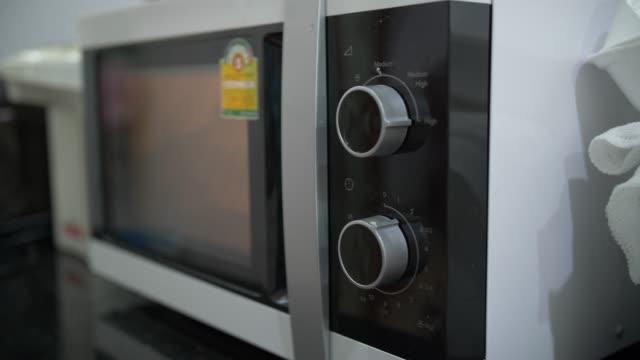年配の女性はキッチン ルームでソーセージを調理 - 電子レンジ点の映像素材/bロール