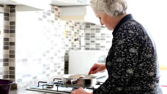 vídeos y material grabado en eventos de stock de mujer senior de cocina - cocina doméstica
